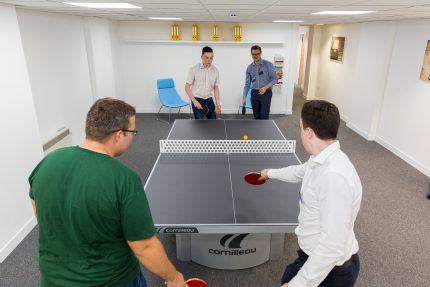 Co-workers playing table tennis