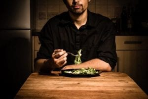 man eating salad - afraid of eating out alone