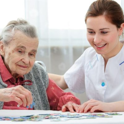 female domiciliary carer helping elderly woman at home