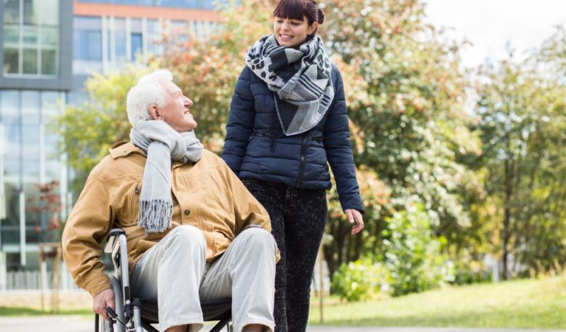 home care tailored activities by female carer with senior patient in wheelchair